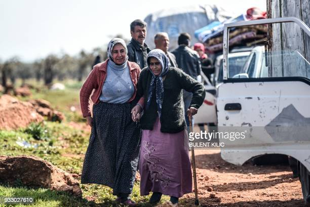 Syrian women arrive at a check point in the village of Anab ahead of crossing to the Turkishbacked Syrian rebels side on March 17 as civilians flee...