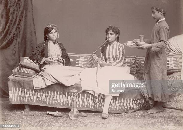 Syrian women being waited on by boy smoking from a hookah pipe