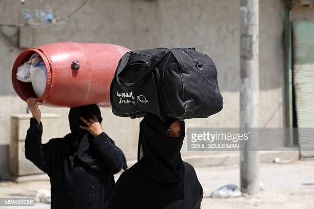 Syrian women carry items on their heads on a street in the northern Syrian town of Manbij as civilians go back to their homes on August 14 2016 more...