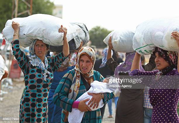 Syrian women carry their belongings as a group of Syrian Kurdish people fled from the clashes between Islamic State of Iraq and the Levant and Syrian...