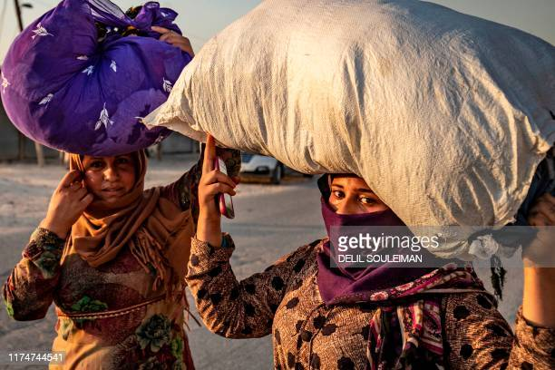 TOPSHOT Syrian women carry their belongings over their heads as Arab and Kurdish civilians flee amid Turkish bombardment on Syria's northeastern town...