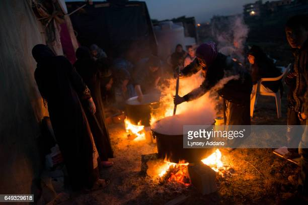 Syrian women prepare a meal for the funeral of a Free Syrian Army fighter who had been killed across the border in Aleppo while his family members...