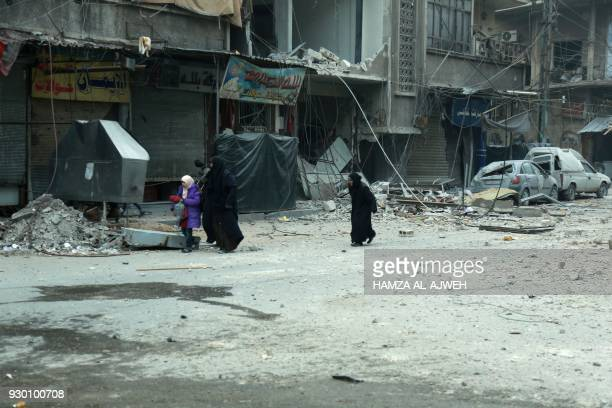 Syrian women run for cover following Syrian government bombardment on the town of Douma in the rebelheld enclave of Eastern Ghouta on the eastern...