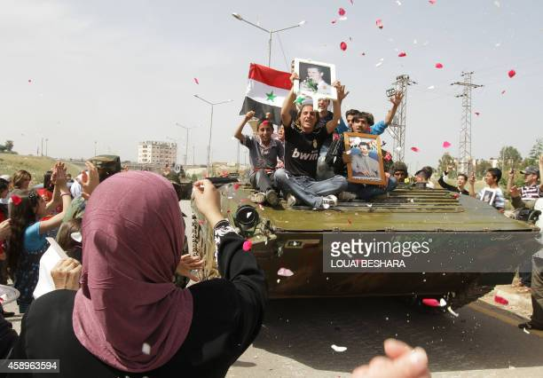 S Syrian women shower army troops with rose petals and rice as youths holding up portraits of President Bashar alAssad ride on an army tank pulling...