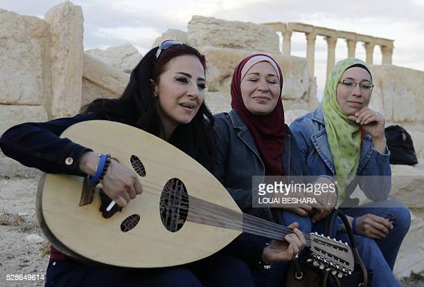 Syrian women sing and play the oud during a visit to the historical site of the ancient theatre of Syria's ravaged Palmyra on May 6 2016 ahead of a...