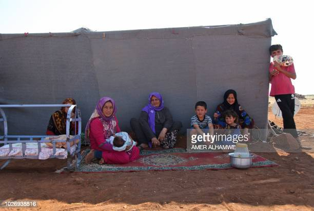 Syrian women sit with children outside a tent at a camp for displaced civilians fleeing from advancing Syrian government forces close to a Turkish...