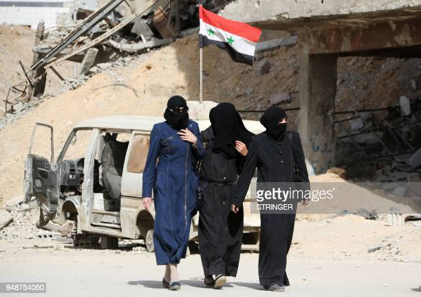 Syrian women walk along a street in the former rebelheld Syrian town of Douma on the outskirts of Damascus on April 19 five days after the Syrian...