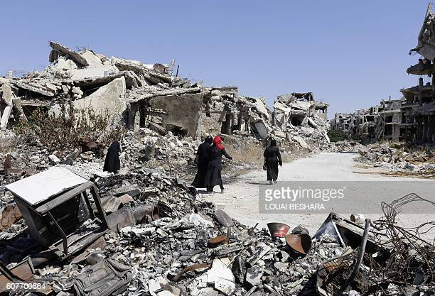 Syrian women walk between destroyed buildings in the governmentheld Jouret alShiah neighbourhood of the central Syrian city of Homs on September 19...