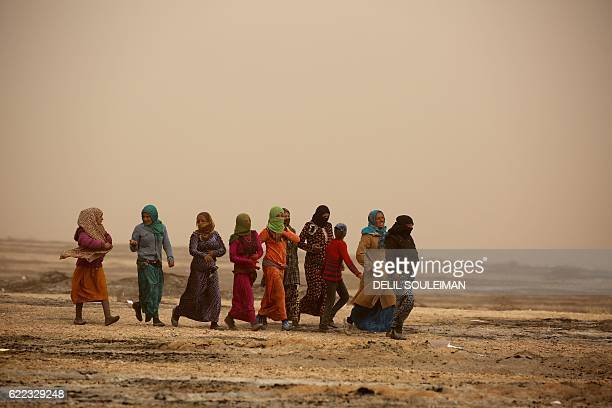 Syrian women walk during a sandstorm near at a temporary refugee camp in the village of Ain Issa, housing people who fled Islamic State group's...