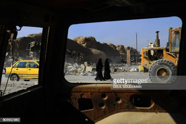 TOPSHOT Syrian women walk in the northern Syrian city of Raqa on January 16 2018 after a huge military operation led on the ground by Kurdish...