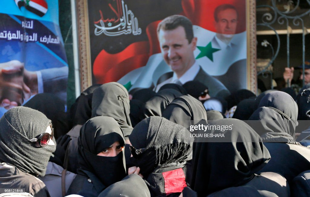 Syrian women walk past a large portrait of President Bashar al-Assad and a watermarked portrait of his late father and former President Hafez al-Assad as they queue to attend the government-sponsored 'Ghouta Shopping Festival', in the Eastern Ghouta town of Douma, on the eastern outskirts of the capital Damascus, on May 13, 2018.