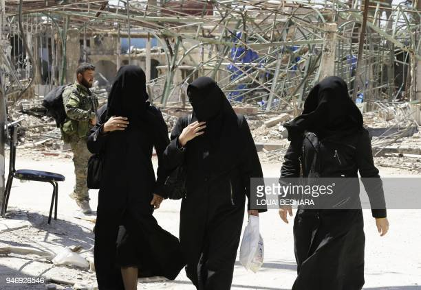 Syrian women wearing the niqab walk along a destroyed street in Douma on the outskirts of Damascus on April 16 2018 during an organised media tour...