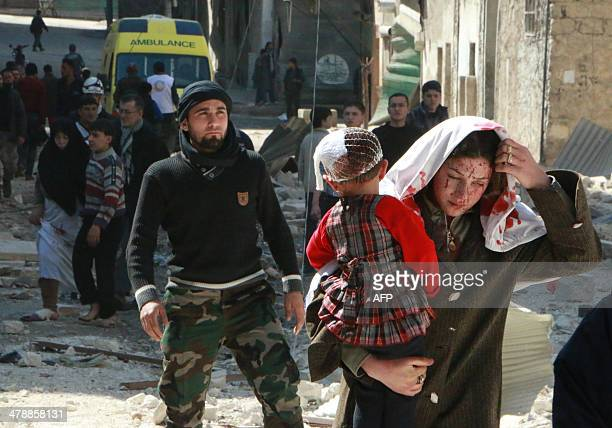 Syrian women with blood on her face carries a child following a reported air strike by government forces on March 15, 2014 on the northern city of...