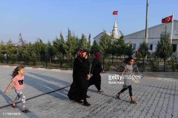 Syrian women with children walk through the Boynuyogun refugee camp on September 16, 2019 in Hatay, Turkey. Turkey's president, Recep Tayyip Erdogan,...