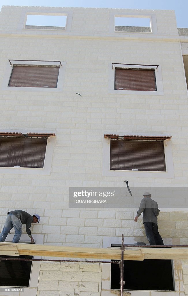 MABARDI Syrian workers construct a building in Damascus on May 20, 2010