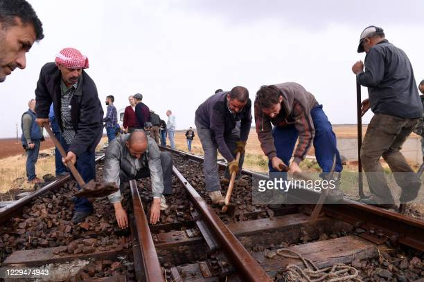 Syrian workers rehabilitate rails near Idlib province's southeastern town of Sinjar, during the first train test ride from Aleppo's railway station,...