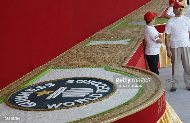 A Syrian workers stand next to a mosaic of traditional Arabic sweets measuring 112 meters long which entered the Guiness Book of World Records as the...
