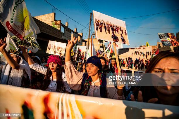 Syrian Yazidi women dressed in traditional clothing march with banners and pictures during a demonstration in the northeastern town of Amude, about...