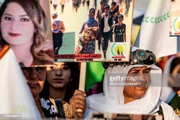 Syrian Yazidis women march with pictures during a demonstration in the northeastern town of Amude, about 28 kilometres west of Qamishli near the...