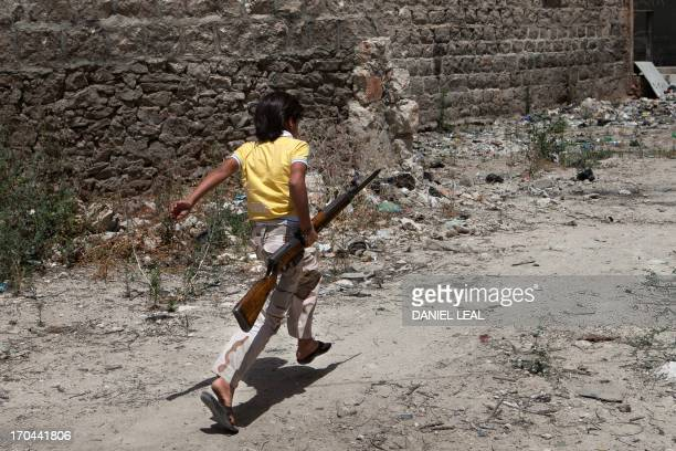 A Syrian young boy runs holding an old rifle as he helps fighters belonging to the Martyrs of Maaret alNuman battalion on June 13 2013 in the...