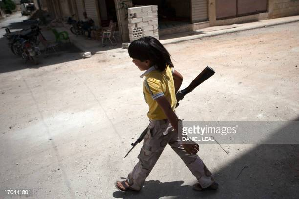 A Syrian young boy walks holding an old rifle as he helps fighters belonging to the Martyrs of Maaret alNuman battalion on June 13 2013 in the...