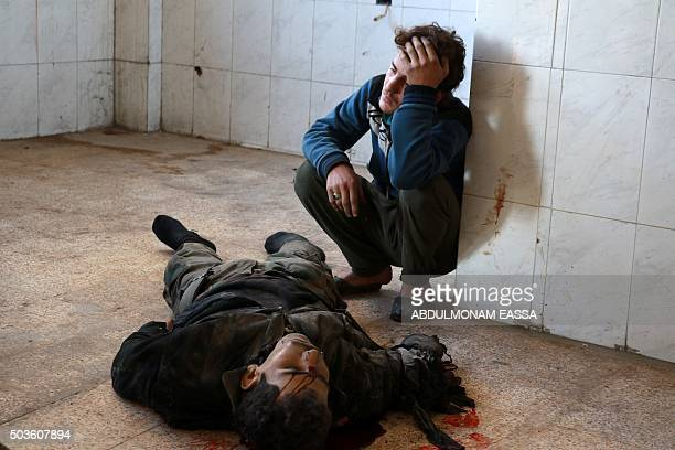 A Syrian young man mourns next to a body at a makeshift hospital following a reported airstrike by Syrian government forces in Damascus' rebelheld...
