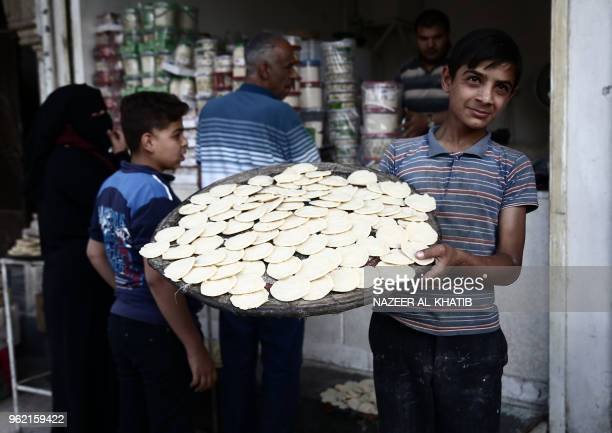 Syrian youth carries a tray of 'Qatayef' traditional pancakes that are popular during the Muslim fasting month of Ramadan in the northern town of...