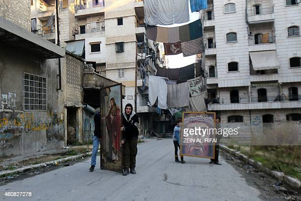 Syrian youth carry religious paintings heading to a Catholic church before Christmas celebrations on December 24 2014 in the rebelheld side of the...