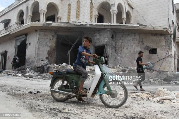 A Syrian youth on a scooter looks at the site of an airstrike by Syrian regime forces in Maar Shurin on the outskirts of Maaret alNuman in northwest...