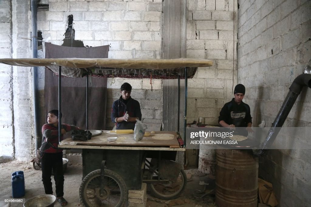 Syrian youth prepare bread as they take shelter inside a building in Haza, in the besieged Eastern Ghouta region on the outskirts of the capital Damascus on February 27, 2018. A humanitarian 'pause' announced by Russia in Syria's deadly bombardment of Eastern Ghouta struggled to take hold, with fresh violence erupting and no sign of aid deliveries or residents leaving the besieged enclave. /