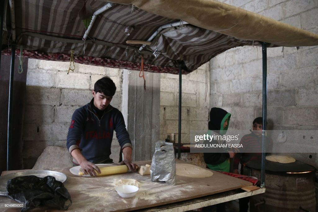 Syrian youth prepare bread as they take shelter inside a building in Haza, in the besieged Eastern Ghouta region on the outskirts of the capital Damascus on February 27, 2018. A humanitarian 'pause' announced by Russia in Syria's deadly bombardment of Eastern Ghouta struggled to take hold, with fresh violence erupting and no sign of aid deliveries or residents leaving the besieged enclave. / AFP PHOTO / ABDULMONAM EASSA / The erroneous mention[s] appearing in the metadata of this photo by ABDULMONAM EASSA has been modified in AFP systems in the following manner: [Haza] instead of [Hamouria]. Please immediately remove the erroneous mention[s] from all your online services and delete it (them) from your servers. If you have been authorized by AFP to distribute it (them) to third parties, please ensure that the same actions are carried out by them. Failure to promptly comply with these instructions will entail liability on your part for any continued or post notification usage. Therefore we thank you very much for all your attention and prompt action. We are sorry for the inconvenience this notification may cause and remain at your disposal for any further information you may require.