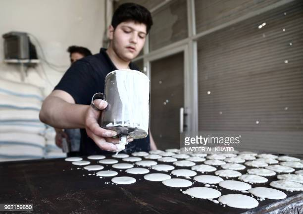 A Syrian youth prepares Qatayef traditional pancakes that are popular during the Muslim fasting month of Ramadan in the northern town of alBab on May...