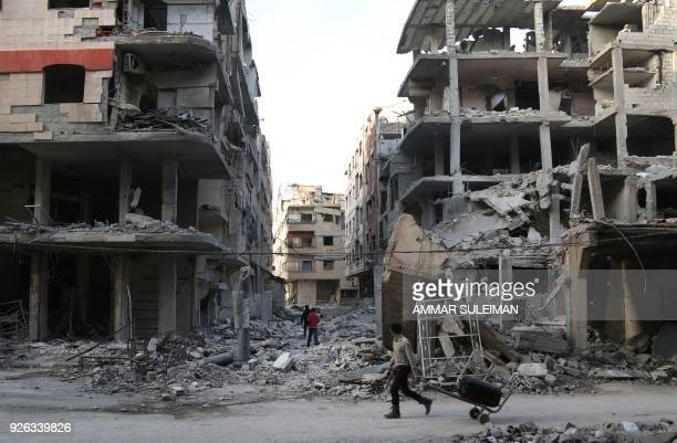 Syrian youth pulls a cart as he walks down a street past destroyed buildings in the rebelheld besieged town of Ayn Tarma in the eastern Ghouta region...