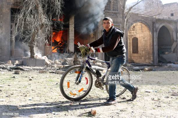 Syrian youth pushes his bicycle past a burning house on November 19 2016 following a reported air strike on Aleppo's rebelheld neighbourhood of Bab...