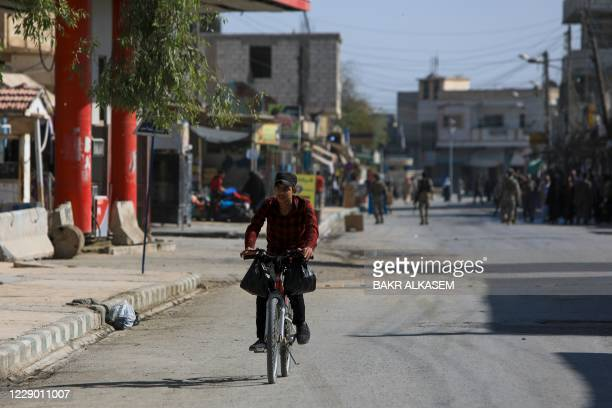Syrian youth rides his bicycle in the rebel-controlled town of Tal Abyad in Syria's northern Raqa province, on October 11, 2020. - UN High...