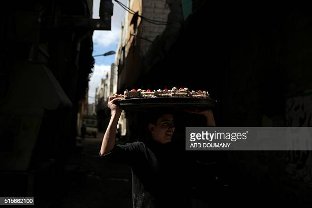 A Syrian youth sells cakes on a street in the rebelheld suburb of Tishreen on the outskirts of the capital Damascus on March 14 2016 / AFP / Abd...