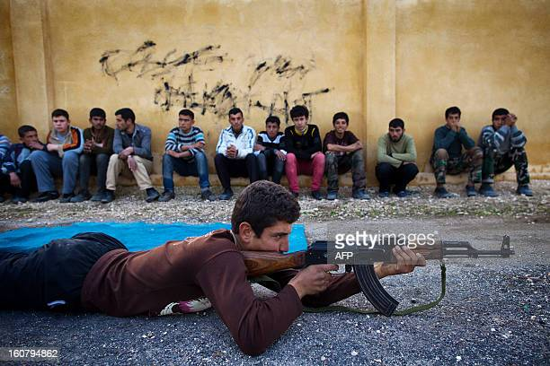 Syrian youth Sobhi holds an AK47 assault rifles as he takes part in a military training on January 23 21013 at a former school turned into a military...