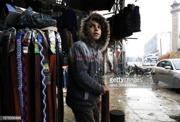 Syrian youth stands outside a shop in the northern Syrian town of Manbij, controlled by Kurdish-dominated Syrian Democratic Forces , on December 26,...