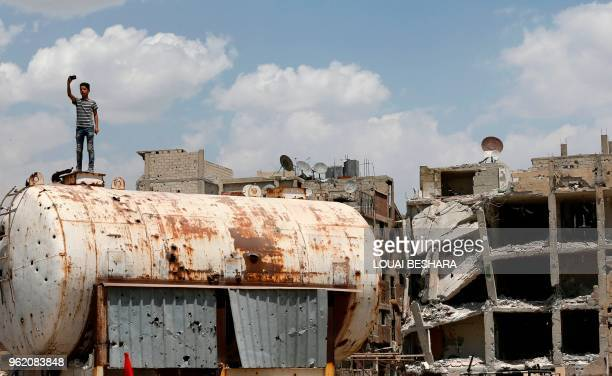 Syrian youth takes a photo on top of a bulletriddled water container on the destroyed Thalateen Street in the Yarmuk Palestinian refugee camp on the...
