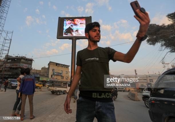 Syrian youth takes a selfie picture with a billboard behind him showing French President Emmanuel Macron presented as a dog, in the northwestern city...