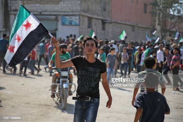 A Syrian youth waves an opposition flag during a demonstration against the Syrian government in the rebelheld town of Hazzanu about 20 kilometres...
