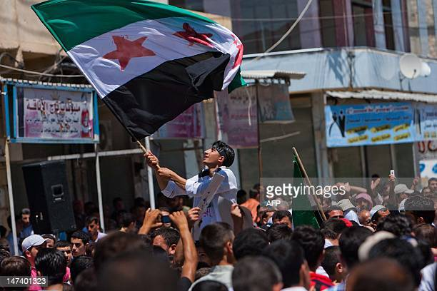 A Syrian youth waves the Syrian revolutionary flag during an antigovernment demonstration after Friday prayers on June 29 in the rebelcontrolled...
