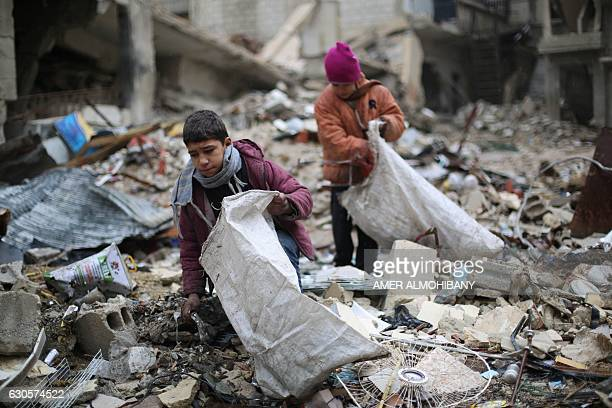 TOPSHOT Syrian youths collect wood from rubble to be used for heating and cooking on December 27 in the Damascus rebelheld eastern suburb of Zamalka...