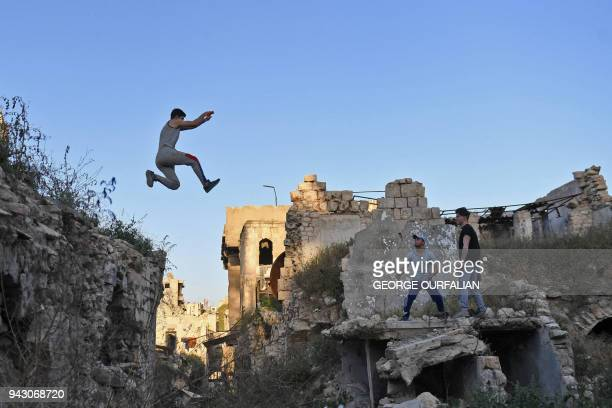 TOPSHOT Syrian youths practise parkour in Aleppo northern Syria on April 7 2018 In the absence of special facilities and equipment for the sport such...