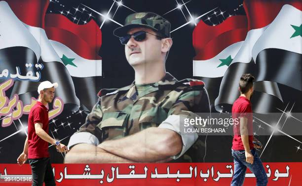 Syrian youths walk past a billboard showing a picture of Syrian President Bashar alAssad wearing sunglasses while dressed in a Field Marshal's...