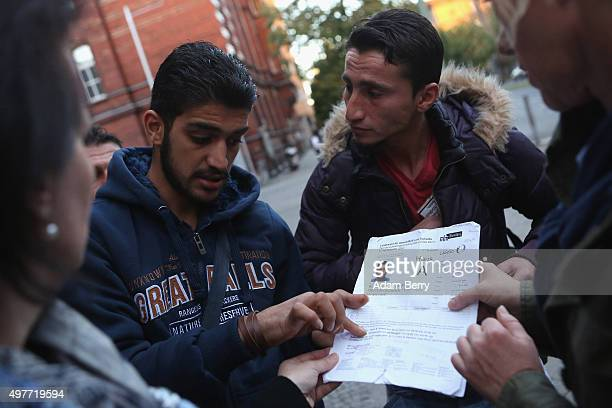 Syrianborn Palestinian refugee Mohammed Al Sebaai shows some locals his refugee identification papers as he waits outside the LaGeSo State Office for...