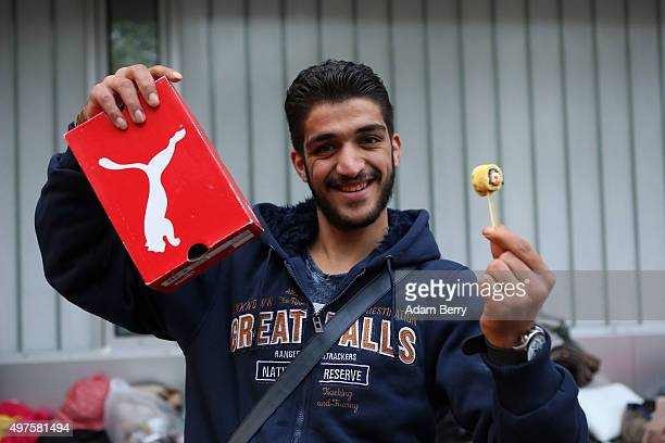 Syrianborn Palestinian refugee Mohammed Al Sebaai shows the box of a pair of donated shoes as well as a canape donation from a caterer as he waits...