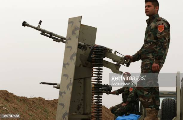 SyrianKurdish Peshmerga fighters and members of the Rojava Forces Defence Units hold a position in the town of Faysh Khabur which lies in Iraq's...