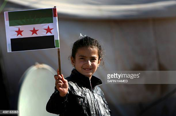 A SyrianKurdish refugee girl poses for a photograph with the preBaath Syrian flag now used by the Syrian opposition at the Quru Gusik refugee camp 20...