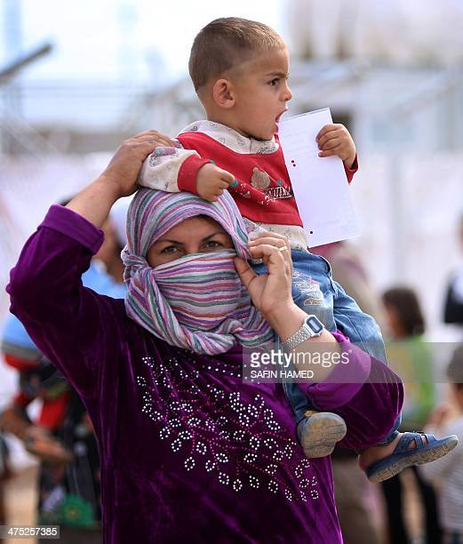 A SyrianKurdish refugee holds her child as she queues to receive aid kits on February 27 2014 at the Qushtapa refugee camp 15 kilometers South of...